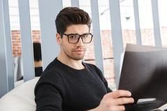Jeune homme sûr d'affaires travaillant au bureau photographie stock