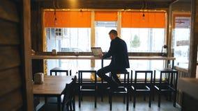 Jeune homme sûr dans la tenue de détente travaillant sur l'ordinateur portable tout en se reposant près de la fenêtre en bureau o clips vidéos