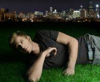Jeune homme s'étendant sur l'herbe Photographie stock libre de droits