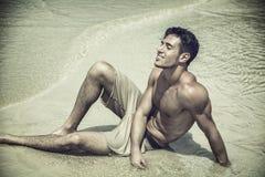 Jeune homme s'étendant sur la plage par l'océan Photo libre de droits