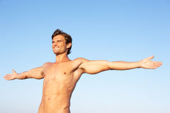 Jeune homme s'étirant sur la plage Image libre de droits