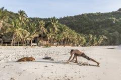 Jeune homme s'étirant sur une plage tropicale pendant le matin Image stock