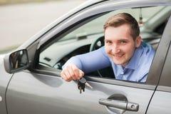 Jeune homme s'asseyant à l'intérieur de la nouvelle voiture avec des clés Sourire Photo stock