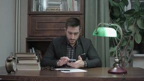 Jeune homme s'asseyant à sa table d'étude avec des livres et à l'aide du téléphone portable banque de vidéos