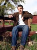 Jeune homme s'asseyant Photo stock