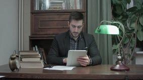 Jeune homme s'asseyant au bureau avec des livres utilisant le comprimé numérique dans le bureau de chambre à la maison banque de vidéos