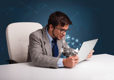 Jeune homme s'asseyant au bureau et tapant sur l'ordinateur portable avec le netwo social Image libre de droits
