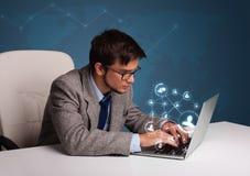Jeune homme s'asseyant au bureau et tapant sur l'ordinateur portable avec le netwo social Images stock