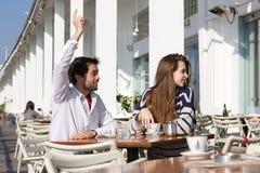 Jeune homme s'asseyant au café extérieur avec le bras augmenté demandant le serveur Photographie stock