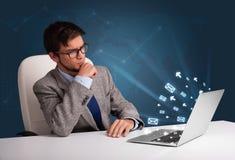 Jeune homme s'asseyant au DEST et dactylographiant sur l'ordinateur portable avec l'icône de message Images libres de droits