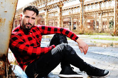 Jeune homme, s'asseyant au sol, fond urbain Image libre de droits