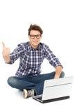 Jeune homme s'asseyant avec l'ordinateur portatif image stock