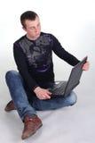 Jeune homme s'asseyant avec le cahier Image libre de droits