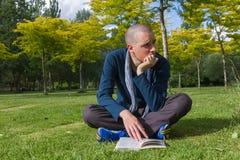 Jeune homme s'asseyant avec le livre en parc Images libres de droits