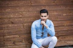 Jeune homme s'asseyant contre le mur en bois photographie stock