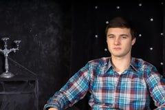 Jeune homme s'asseyant dans la chaise de dos de noir de peluche haut Image stock