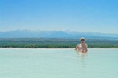Jeune homme s'asseyant dans la piscine thermique avec le Mountain View Photographie stock