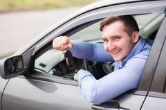 Jeune homme s'asseyant dans la voiture tenant des clés de voiture Image libre de droits