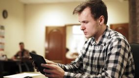 Jeune homme s'asseyant dans le bureau banque de vidéos