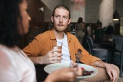 Jeune homme s'asseyant dans le restaurant et parlant avec la fille Garçon s'asseyant au café avec le verre de l'eau à disposition Photos libres de droits