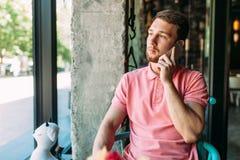 Jeune homme s'asseyant en café avec l'ordinateur portable et le téléphone, fonctionnement, achats en ligne, hippie image libre de droits