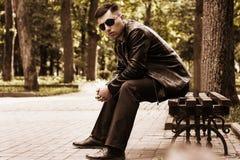 Jeune homme s'asseyant en parc sur un banc dans les lunettes de soleil et une veste en cuir images libres de droits
