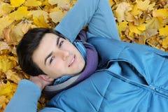 Jeune homme s'asseyant en stationnement. Images stock