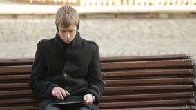 Jeune homme s'asseyant et dactylographiant sur le comprimé banque de vidéos