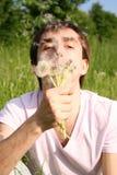Jeune homme s'asseyant et soufflant au bouquet de pissenlit Image libre de droits