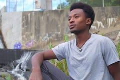 Jeune homme s'asseyant près des aspirations de pensée songeuses de rivière images stock