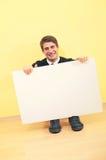 Jeune homme s'asseyant retenant un panneau-réclame blanc images libres de droits