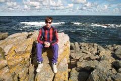 Jeune homme s'asseyant sur des roches Photo stock