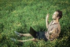 Jeune homme s'asseyant sur l'herbe et méditant Ordinateur portable sur son kne photo stock