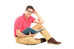 Jeune homme s'asseyant sur l'étage et affichant un livre Photo stock
