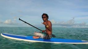 Jeune homme s'asseyant sur la planche de surf L'eau calme de l'Océan Indien L'eau étonnante de turquoise de beauté et ciel bleu a banque de vidéos