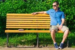 Jeune homme s'asseyant sur le banc Image stock