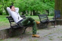 Jeune homme s'asseyant sur le banc en parc Photographie stock libre de droits