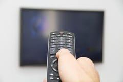 Jeune homme s'asseyant sur le divan observant une partie de football à la TV Images stock