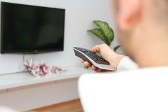 Jeune homme s'asseyant sur le divan observant une partie de football à la TV Photographie stock libre de droits