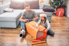Jeune homme s'asseyant sur le plancher avec la petite fille et la grande boîte de emballage du présent Ils sont concentrés sur le photographie stock