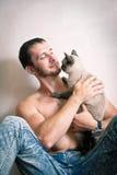 Jeune homme s'asseyant sur le plancher avec son chat Photographie stock