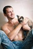 Jeune homme s'asseyant sur le plancher avec son chat Photo libre de droits