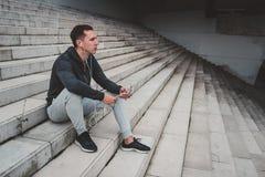 Jeune homme s'asseyant sur le pont moderne dans la ville, utilisant son smartphone Photos libres de droits