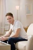 Jeune homme s'asseyant sur le sofa à la maison Photo stock