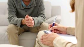 Jeune homme s'asseyant sur le sofa parlant à son thérapeute banque de vidéos