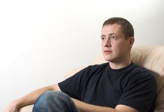 Jeune homme s'asseyant sur le sofa regardant la TV Images libres de droits