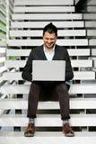 Jeune homme s'asseyant sur les escaliers utilisant l'ordinateur portable Images stock