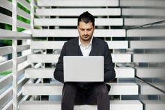 Jeune homme s'asseyant sur les escaliers utilisant l'ordinateur portable Image stock