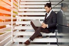Jeune homme s'asseyant sur les escaliers utilisant l'ordinateur portable Photographie stock libre de droits