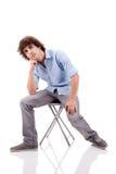 Jeune homme, s'asseyant sur un banc Photographie stock libre de droits